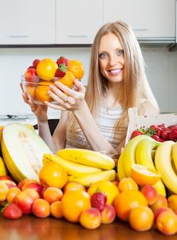 Glückliche frau mit verschiedenen früchten