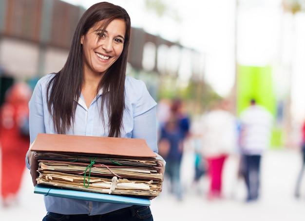 Glückliche frau mit vielen papieren und ordnern