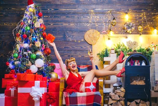 Glückliche frau mit weihnachtsgeschenk über weihnachten innenhintergrund schönheit weihnachten modemodell gi...