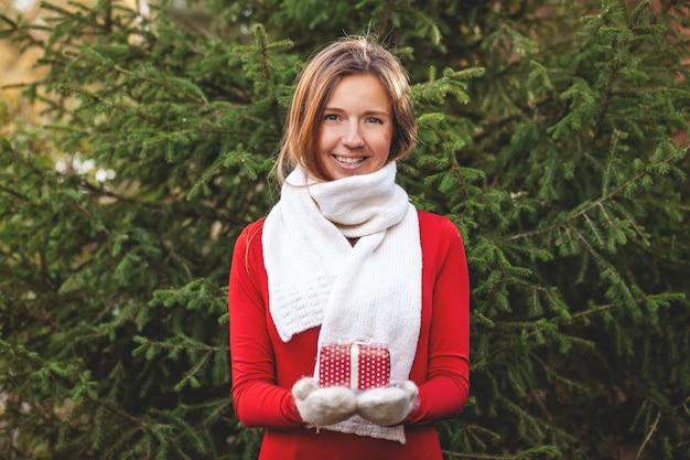 Glückliche frau mit weihnachtsgeschenkbox auf ihren händen