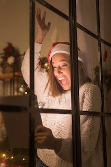 Glückliche frau mit weihnachtsmütze durch fenster, das tablette hält
