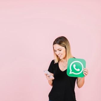 Glückliche frau mit whatsapp ikone unter verwendung des mobiltelefons