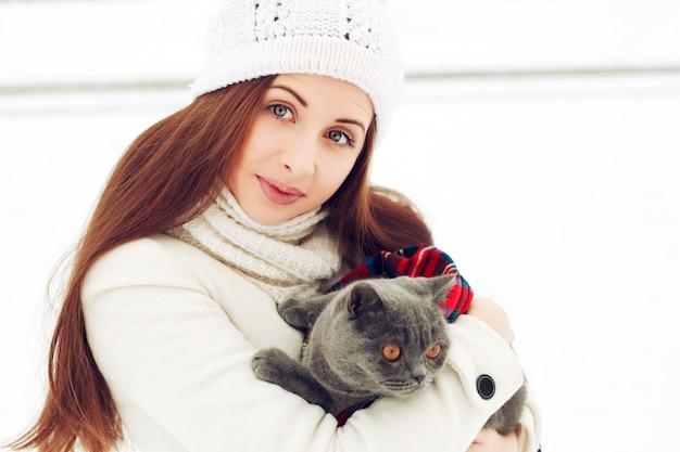 Glückliche frau mit wollmütze und umarmt ihre katze