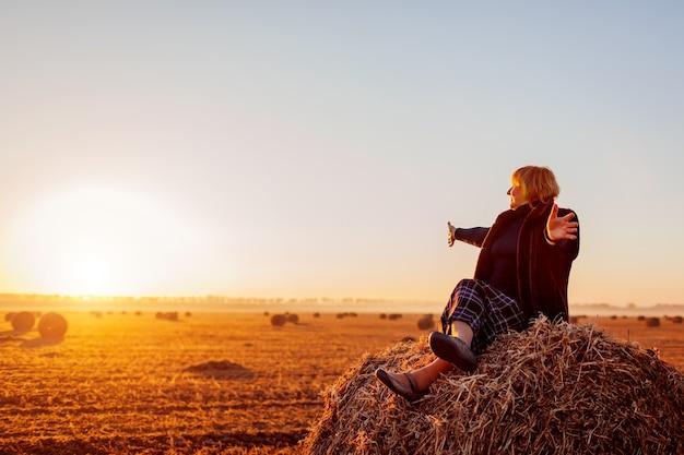 Glückliche frau mittleren alters, die auf heuhaufen im herbstfeld mit geöffneten armen sitzt. entspannen und die natur bei sonnenuntergang bewundern