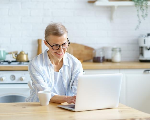 Glückliche frau mittleren alters, die etwas auf der tastatur tippt, während sie zu hause am laptop arbeitet oder lernt