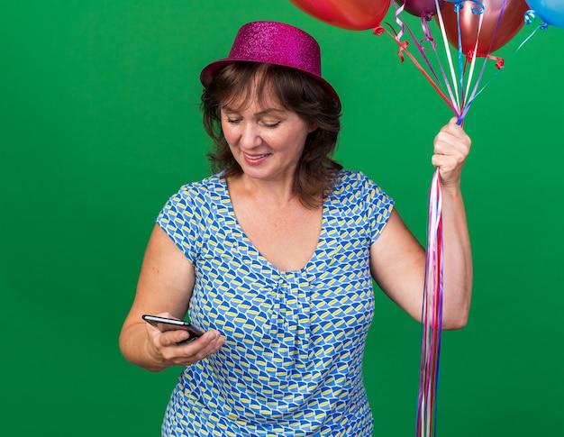 Glückliche frau mittleren alters in partyhut mit bunten luftballons und smartphone, die es mit einem lächeln im gesicht betrachtet und die geburtstagsfeier über grüner wand feiert