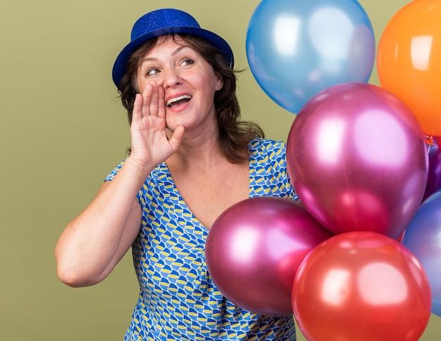 Glückliche frau mittleren alters in partyhut mit einem haufen bunter ballons, die mit der hand in der nähe des mundes rufen oder schreien