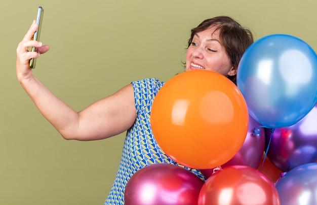 Glückliche frau mittleren alters mit bunten luftballons, die selfie mit dem smartphone machen und fröhlich lächeln