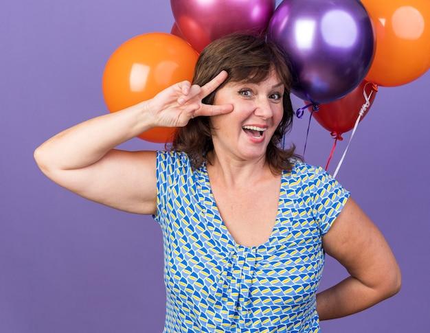 Glückliche frau mittleren alters mit einem haufen bunter luftballons, die ein v-zeichen zeigen, das fröhlich lächelt