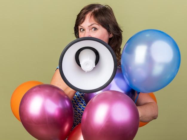 Glückliche frau mittleren alters mit einem haufen bunter luftballons, die zum megaphon schreien