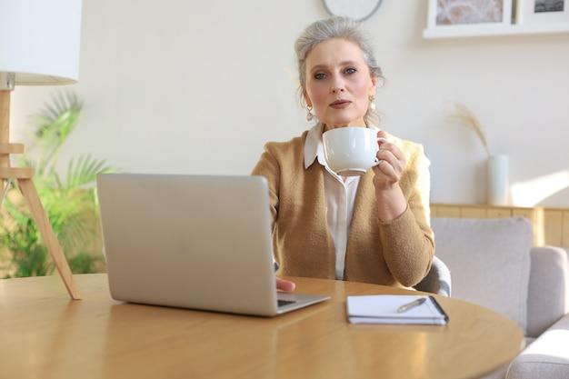 Glückliche frau mittleren alters mit laptop-computer, die zu hause kaffee trinkt.
