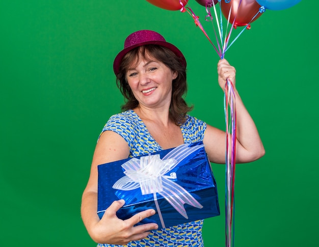 Glückliche frau mittleren alters mit partyhut, die bunte luftballons hält und fröhlich lächelnd die geburtstagsfeier feiert, die über grüner wand steht