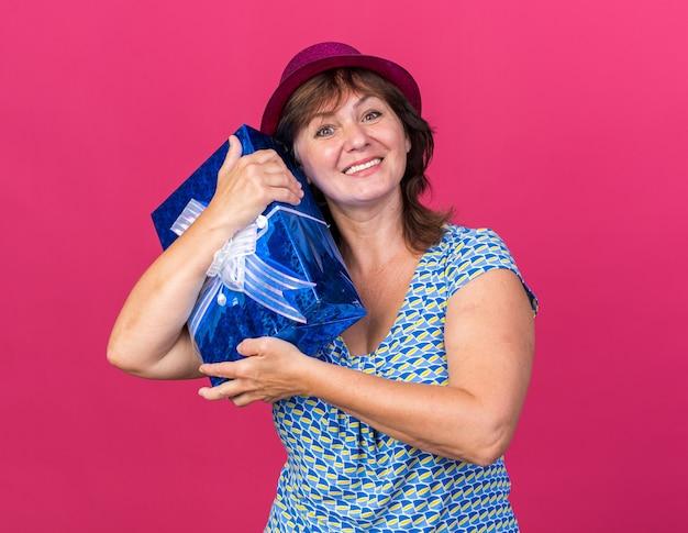 Glückliche frau mittleren alters mit partyhut, die ein geschenk umarmt und fröhlich lächelt