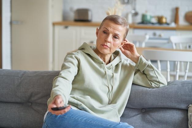 Glückliche frau mittleren alters vor dem fernseher, während sie zu hause auf dem sofa sitzt