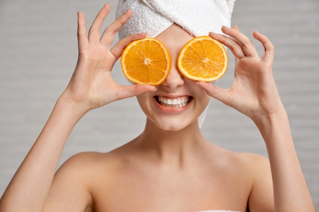 Glückliche frau nach der dusche, die mit frischen orangen aufwirft