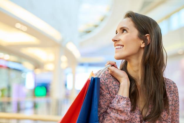 Glückliche frau nach großem einkaufsbummel in der stadt