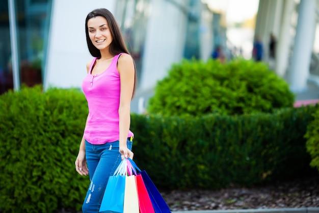 Glückliche frau nahe dem einkaufszentrum, das geschenkbeutel anhält