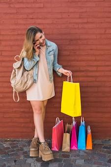 Glückliche frau nahe den hellen einkaufstaschen, die telefonisch sprechen