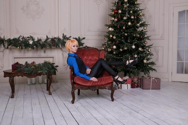 Glückliche frau nahe weihnachtsbaum, neues jahr