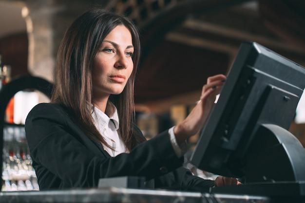 Glückliche frau oder kellner oder manager in der schürze am schalter mit kasse, die an der bar oder im café arbeitet