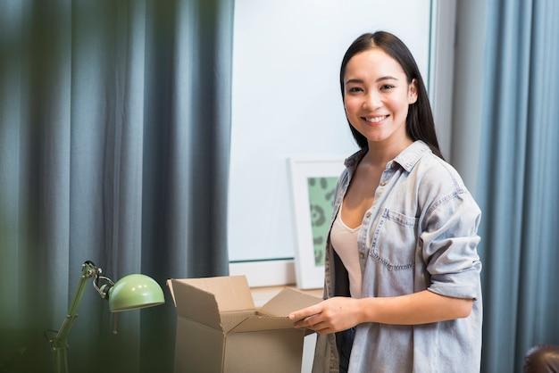 Glückliche frau posiert mit box, die sie nach online-bestellung erhalten hat