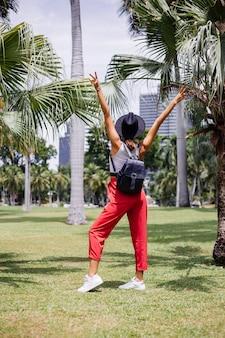 Glückliche frau reisen durch bangkok mit rucksack und genießen schönen sonnigen tag im tropischen park auf grünem grasfeld