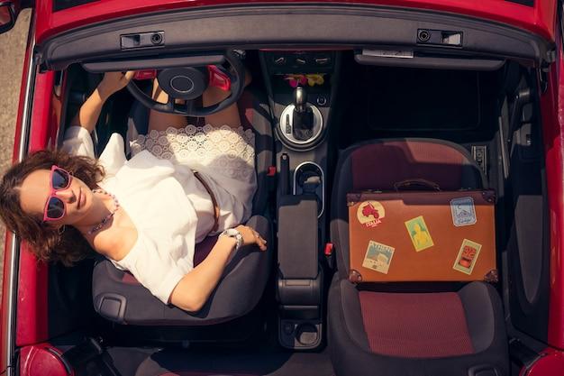 Glückliche frau reisen mit dem auto mädchen, das spaß im roten cabriolet hat sommerurlaub und reisekonzept draufsicht