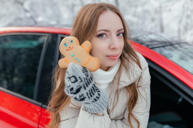 Glückliche frau schaut aus dem autofenster, hält einen keks in form eines mannes in den händen. vor dem hintergrund des winterwaldes.