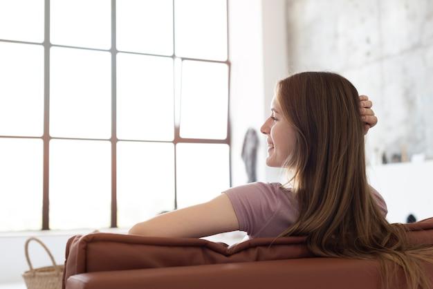 Glückliche frau sitzt auf einer couch