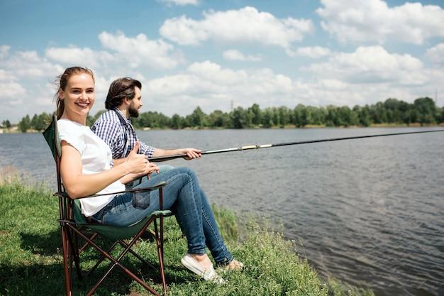 Glückliche frau sitzt im weichen stuhl und schaut. sie lächelt. ihr mann sitzt neben ihr und versucht, mit einer angelrute fische zu fangen.