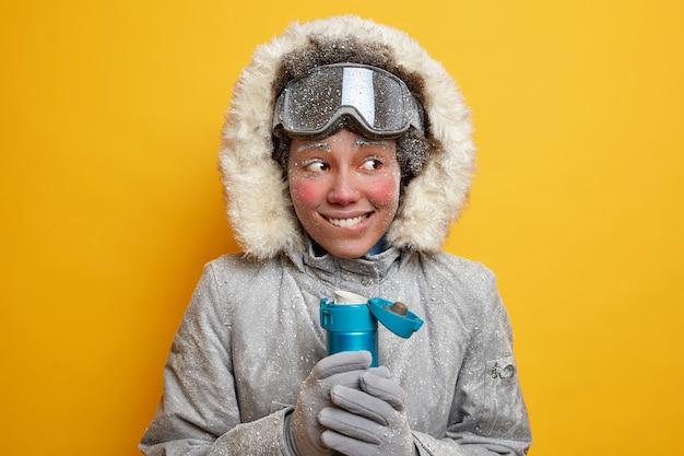 Glückliche frau snowboarder bedeckt mit raureif versucht, während des gefriertages mit heißem getränk in winterkleidung gekleidet zu wärmen hat reise in nordpol hält thermoskanne von tee. extremer saisonaler sport