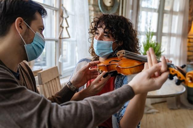 Glückliche frau spielt geige unter den anweisungen des männlichen musiklehrers in maske während des coronavirus zu hause