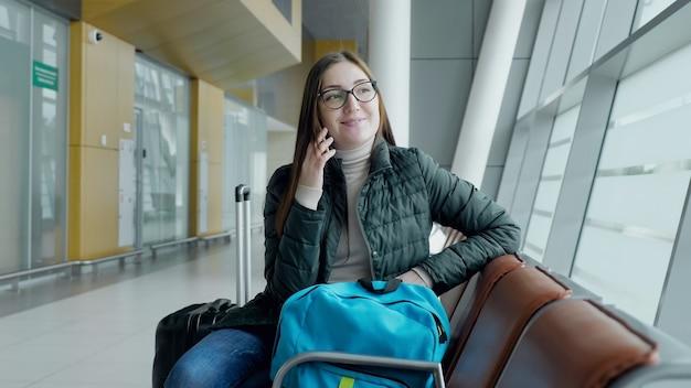 Glückliche frau spricht mit dem handy und wartet auf ihren flug am flughafen