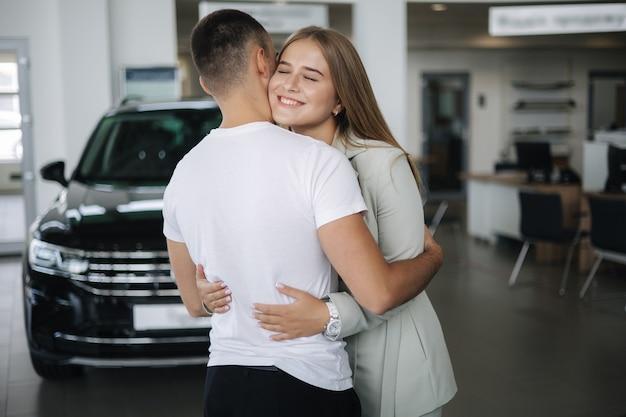 Glückliche frau umarmt seinen mann nach dem autokauf im autohaus mann und frau kaufen ein neues auto