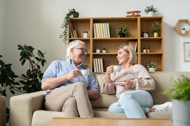 Glückliche frau und ihr älterer vater, die tee trinken, während sie auf der couch sitzen und am wochenende im wohnzimmer plaudern