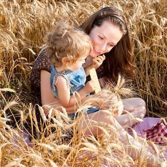 Glückliche frau und kind, die brot im sommerweizenfeld essen