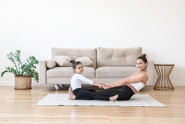 Glückliche frau und kind mädchen zusammen yoga-stretching-training zu hause auf teppich