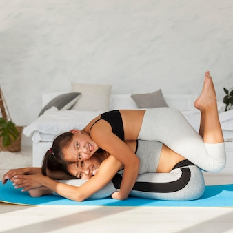 Glückliche frau und mädchen mit yogamatte