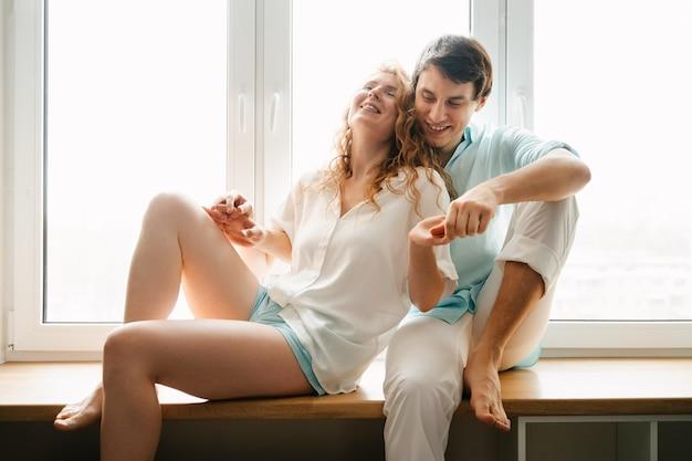 Glückliche frau und mann, die nahe fenster im haus am valentinstag umarmen