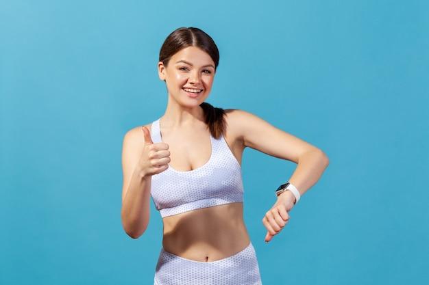 Glückliche frau zeigt daumen hoch und zeigt smartwatch an ihrem handgelenk und überprüft indikatoren