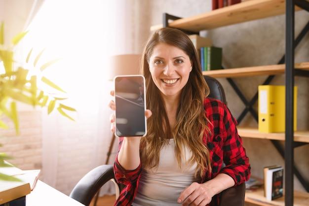 Glückliche frau zeigt etwas in ihrem modernen smartphone