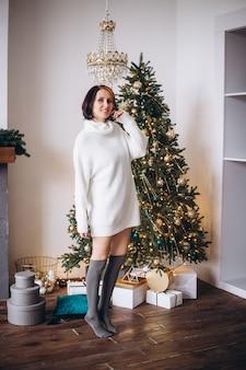Glückliche frau zu hause nahe einem weihnachtsbaum