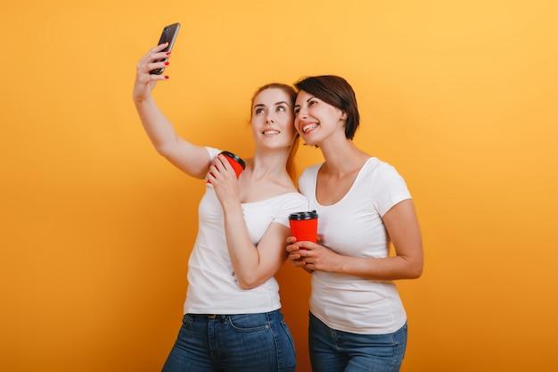 Glückliche frau zwei, die ein papierkaffeeglas hält und machen ein selfie foto