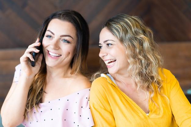 Glückliche frauen, die auf smartphone sprechen und spaß haben