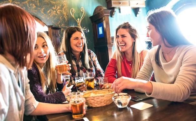 Glückliche frauen, die bier im brauereirestaurant trinken