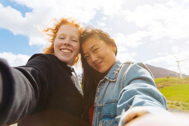 Glückliche frauen, die draußen selfie nehmen
