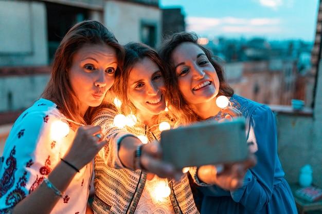 Glückliche frauen, die ein selfie zusammen auf dachparty in der nacht nehmen
