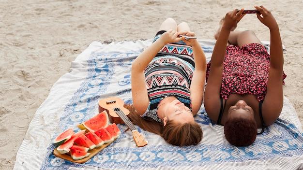 Glückliche frauen, die selfie am strand nehmen