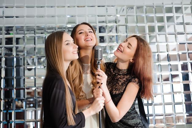 Glückliche frauen, die spaß haben, auf einer party zu singen.