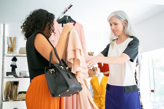 Glückliche frauen, die zusammen einkaufen und ausgewähltes kleid im modegeschäft diskutieren. seitenansicht. konsum- oder einkaufskonzept